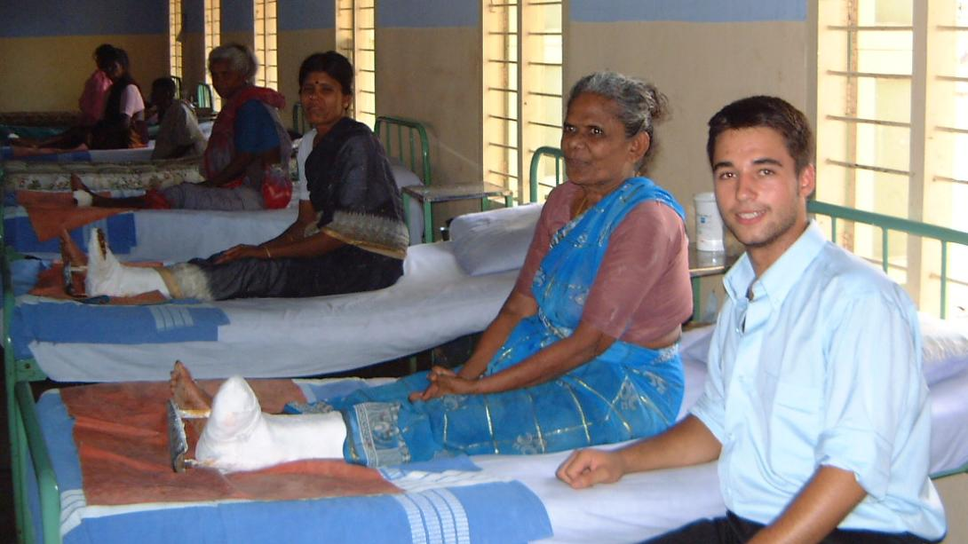 Medical intern sitting next to a local woman who received medical attention on her foot in India.